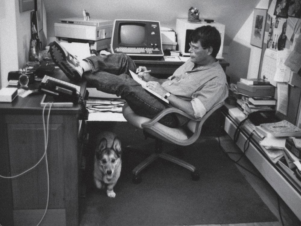 Ecco, King scrive coi piedi poggiati sulla scrivania e un cane accucciato sotto. Ma forse anche no.