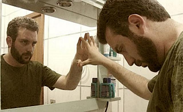 Mi pettino allo specchio con la mano destra. Il mio riflesso si sta pettinando con la stessa mano.