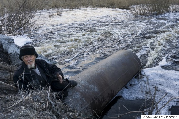 In this photo taken on Thursday, April 7, 2016, an old man fishes in a lake that connects to the nearby Techa River, near the village of Muslyumovo, Chelyabinsk region, Russia, which is polluted with radioactive waste from Mayak nuclear plant. Mayak has been responsible for at least two of the country's biggest radioactive accidents. Worse, environmentalists say, is the facility's decades-old record of using the Arctic-bound waters of the Techa River to dump waste from reprocessing spent nuclear fuel, hundreds of tons of which is imported annually from neighboring nations. (AP Photo/Katherine Jacobsen)